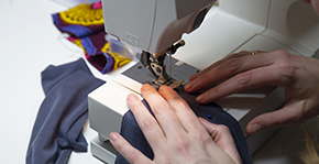 afbeelding twee handen aan een naaimachine met stof